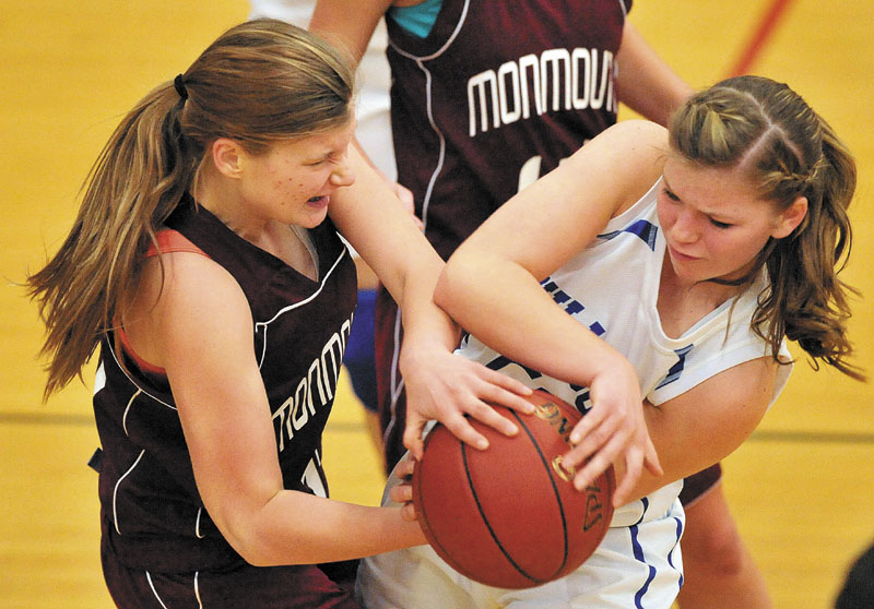 Monmouth Academy's Amanda Anair, left, and Madison Memorial High School's Kirsten Wood, right, battle for the ball in the second quarter Thursday night in Madison. The Bulldogs won 49-30.