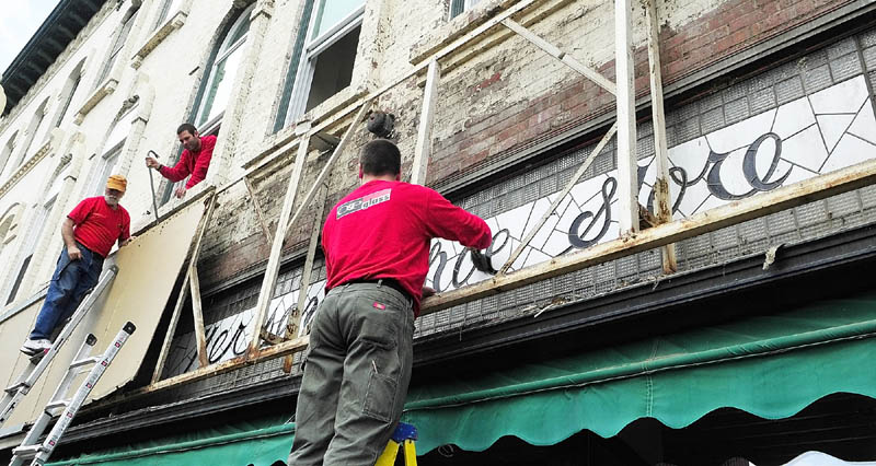 This May 2011 file photo shows Richard Parkhurst, left, and Tobias Parkhurst, of Oakes and Parkhurst Glass, removing the vinyl and metal facade that covered the stained glass window that Glenn Parkhurst, of Stained Glass Express, is cleaning off on Water Street in downtown Augusta. The window says Hersey's Show Store in blue script. The building is owned by Tobias Parkhurst and is home of the Downtown Diner.
