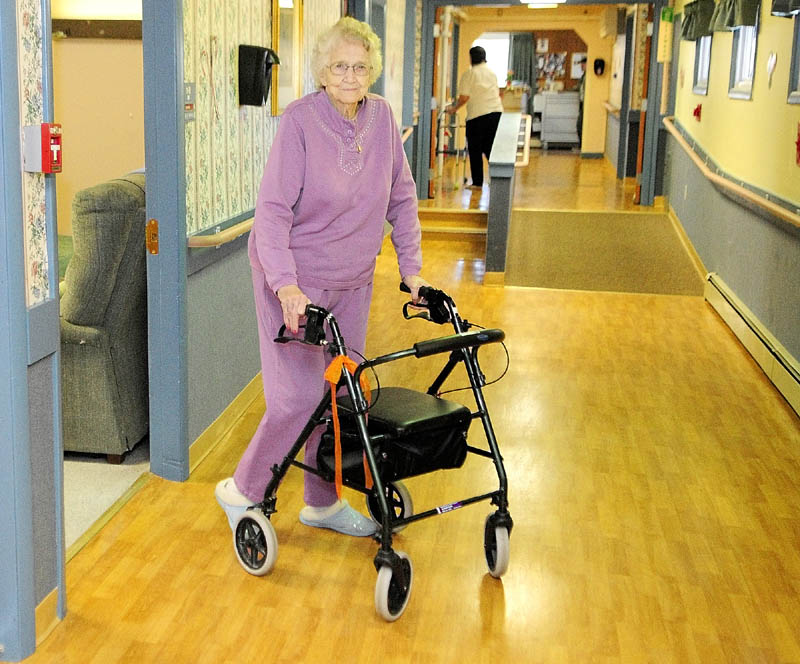 NEEDING SOME HELP: Errie Hasty, 89, walks down the hallway of the Heritage Rehabilitation & Living Center in Winthrop. Hasty moved in almost five years ago when she could no longer manage her medications by herself. Now, she's one of the 4,291 elderly people in the state who would need to find somewhere else to live if the facilities close. Hasty is a widow, and only one of her four children lives in the area.