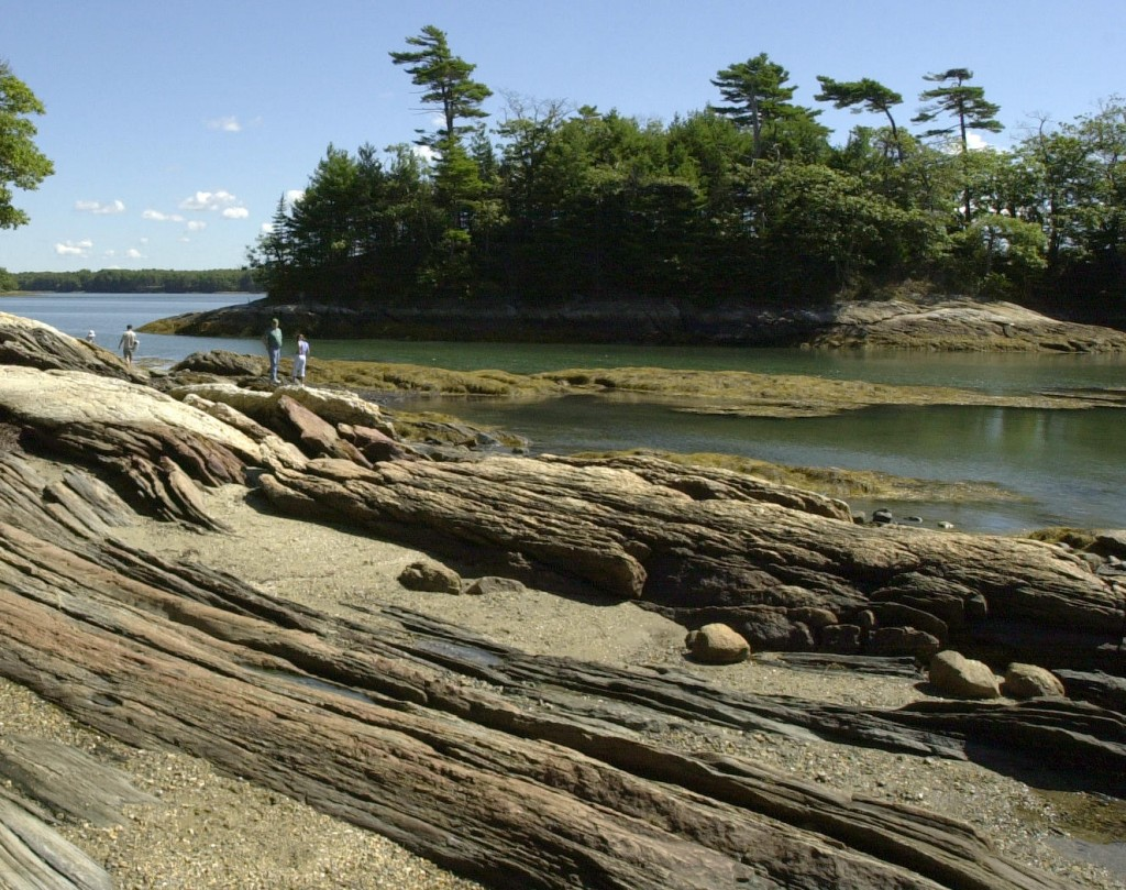 September visitors to Wolfe's Neck Woods State Park in Freeport walk along the rocky shore.