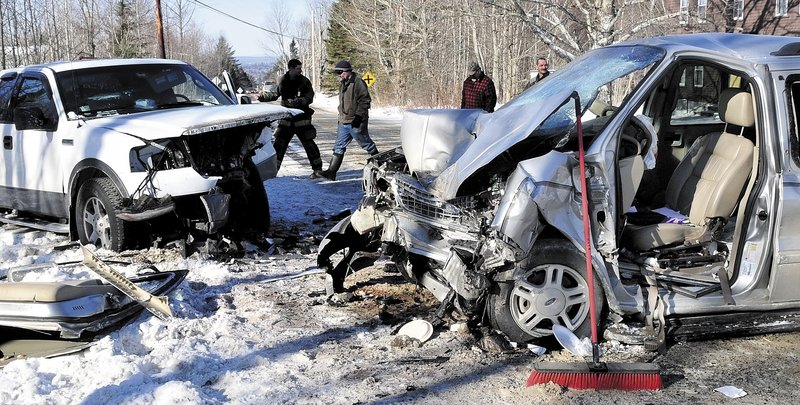 CLEANING UP: Bystanders and firefighters look over the demolished remains of two vehicles that crashed Sunday on the Warren Hill Road in Palmyra. Roger Greenlaw of Newport, operator of the van at right, was transported to Eastern Maine Medical Center by a LifeFlight of Maine helicopter.