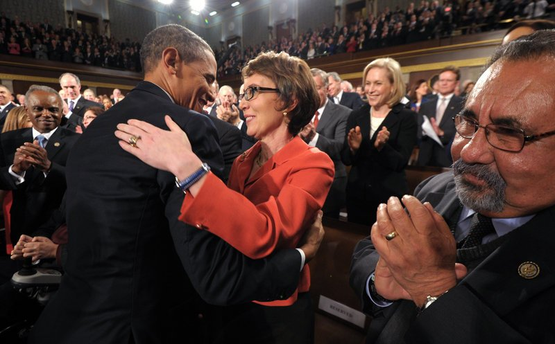 President Obama embraces retiring Rep. Gabrielle Giffords, D-Ariz., who survived an assassination attempt a year ago, as others applaud before his State of the Union address Tuesday night in front of a joint session of Congress in Washington.