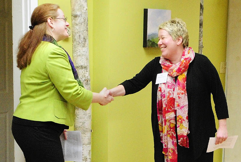 Executive Director Becky DeKeuster, left, shakes hands with Hallowell Mayor Charlotte Warren during a Tuesday news conference at the Wellness Connection of Maine dispensary in Hallowell.