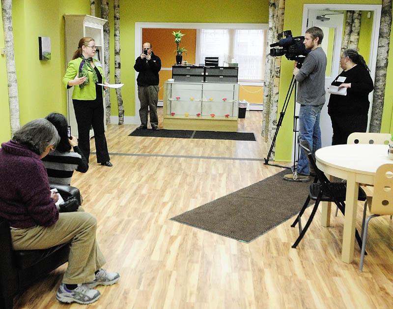 Executive Director Becky DeKeuster speaks during a Tuesday news conference at the Wellness Connection of Maine dispensary in Hallowell. The medicine is stored in and dispensed from the cupboards behind the counter.
