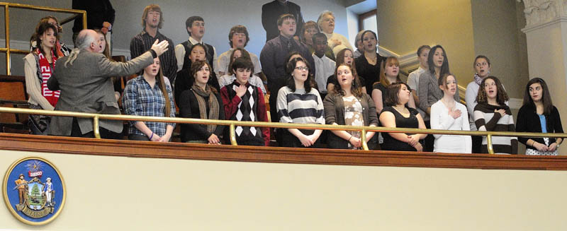 Kevin Rhein directs the Messalonskee High School Chamber Singers as they sing the National Anthem from the gallery in the House chamber on Wednesday morning at the State House in Augusta. The 30 singers, from the high school in Oakland, also sang in rotunda before the session opened at 10 a.m.