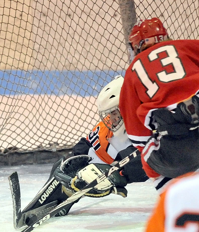 SHOT, SAVE: Skowhegan Area High School goalie Kyle Carrier (30) makes a save on a shot by Cony High School's Galen Casey in the first period of Cony's 2-0 win Saturday at Sukee Arena in Winslow.