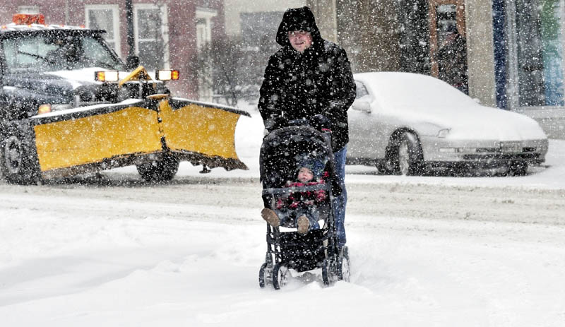 """FINALLY: John Roberts pushes his one-year-old son Patrick in a stroller as snow accumulates in downtown Waterville on Thursday. Roberts said he was glad to see it finally snow this winter and added, """"This is the first time Patrick has seen snow."""""""