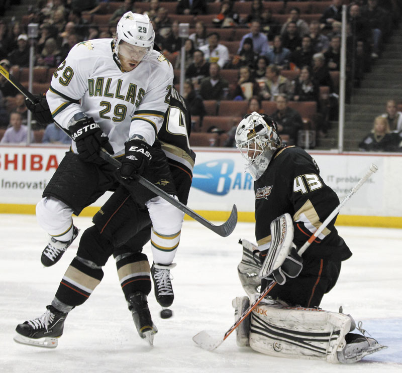 NOT SO FAST: Dallas Stars center Steve Ott, left, jumps out of the way of the puck as Anaheim Ducks goalie Jeff Deslauriers looks on during a game recently. Despite the benefits it would have for teams like the Stars, the NHL players' association has issues with the proposal.