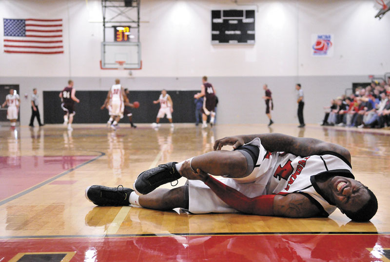 Thomas College's Stanley Greene Jr., 4, lies on the court after injuring his ankle late in the second half against University of Maine on Saturday at Farmington at Mahaney Gymnasium at Thomas College in Waterville. Thomas defeated UMF 81-73.