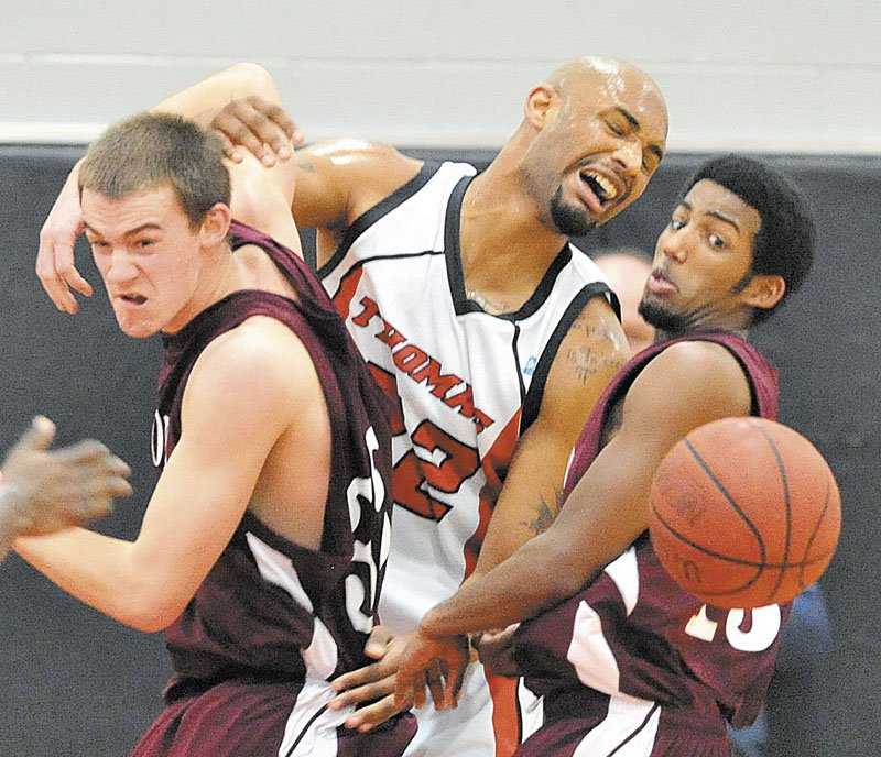 University of Maine at Farmington's Garrett Clemmer, left, and teammate Yusuf Iman battle for the ball with Thomas College's Martin Cleveland, center, in the first half Saturday at Mahaney Gymnasium at Thomas College in Waterville. Thomas defeated UMF 81-73.