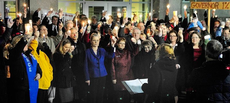 The Rev. Jill Saxby, executive director the Maine Council of Churches, center at podium, speaks during a candlelight vigil outside the State House before Gov. Paul LePage's first State ofthe State address on Tuesday night in Augusta.