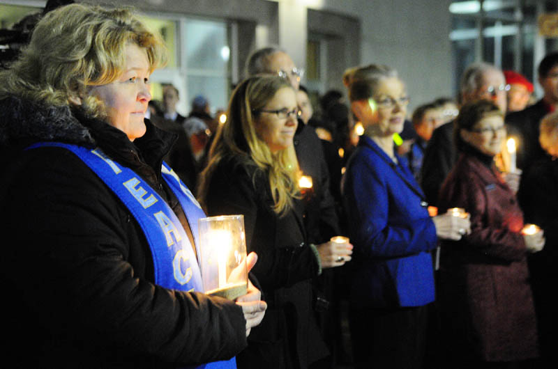 The Rev. Carie Johnsen, the minister of Unitarian Universalist Community Church of Augusta, far left, holds a candle at a vigil outside the State House before Gov. Paul LePage's first State of The State address on Tuesday night in Augusta.