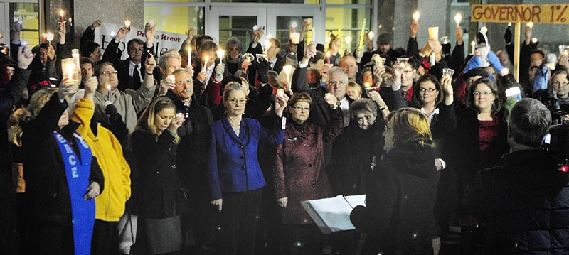 The Rev. Jill Saxby, executive director the Maine Council of Churches, center at podium, speaks during a candlelight vigil outside the State House before Gov. Paul LePage's first State of The State address on Tuesday night in Augusta.