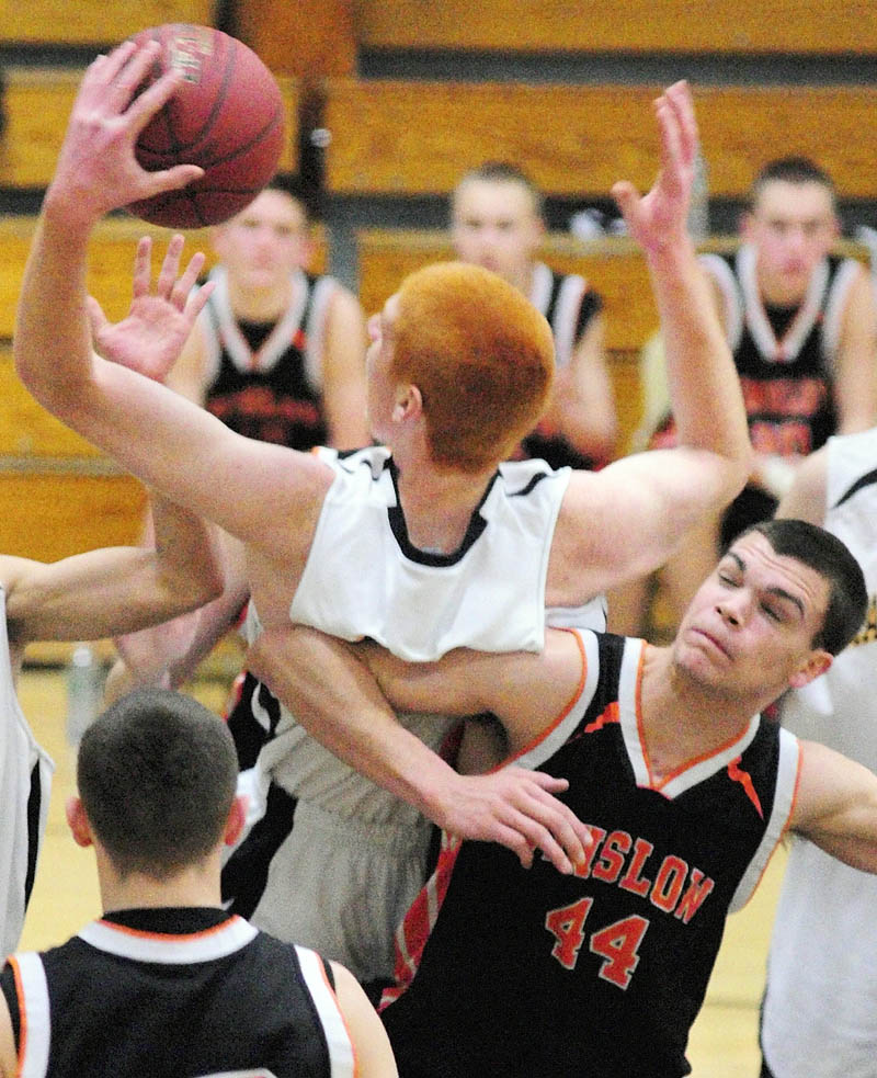 TOUGH IN THE MIDDLE: Marancook's Kyle Boucher, top, and Winslow's Austin Ireland (44) collide going for a rebound during a game Friday night at Maranacook Community School in Readfield.