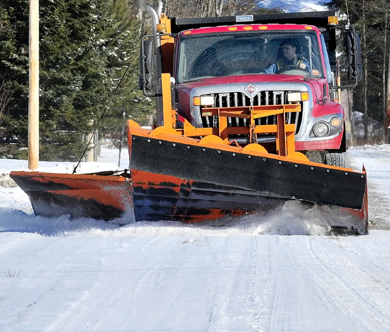 A town or Norridgewock operator of snowplow truck scrapes snow off the Oosoola Road in town last week. Officials throughout the central Maine region are reporting that the high amount of freezing rain an