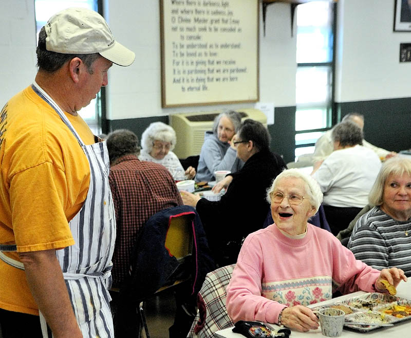 Cook Steve Dodge, left, chats with Lila Sciuk on Wednesday as the Winthrop Hot Meal Kitchen ended a seven-month hiatus and resumed serving daily mid-day meals at St. Francis Xavier Church Hall.