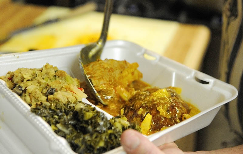 A to-go box is filled with pork roast, stuffing and wilted kale on Wednesday as the Winthrop Hot Meal Kitchen resumed serving daily mid-day meals at St. Francis Xavier Church Hall.