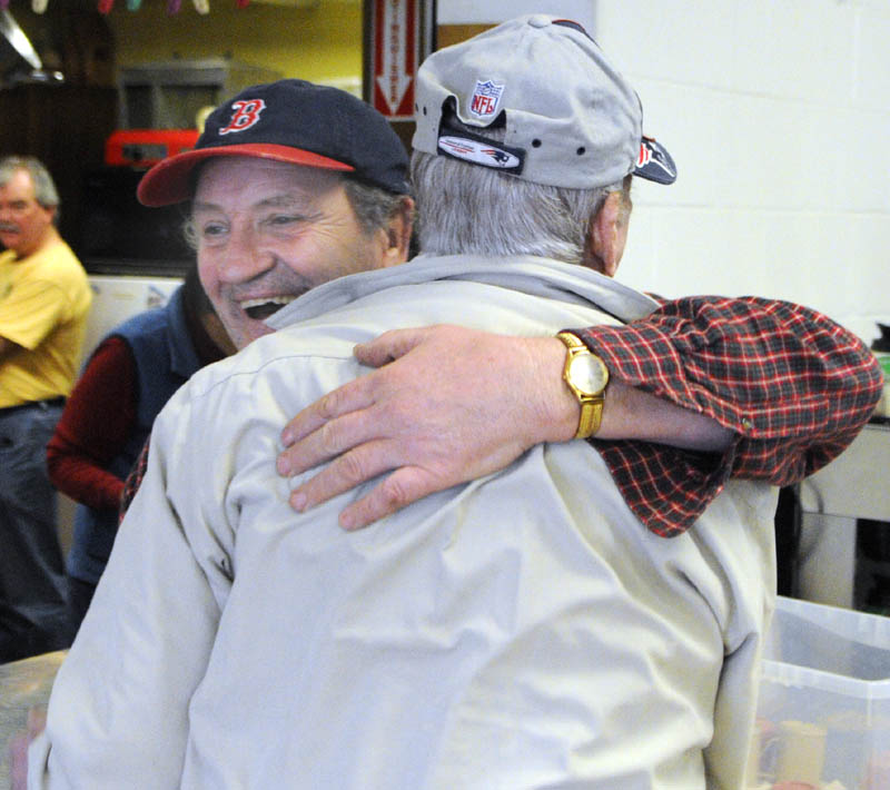Volunteer Joe Cook, left, hugs Jack Everett as he comes in for lunch on Wednesday at the Winthrop Hot Meal Kitchen in the St. Francis Xavier Church Hall.