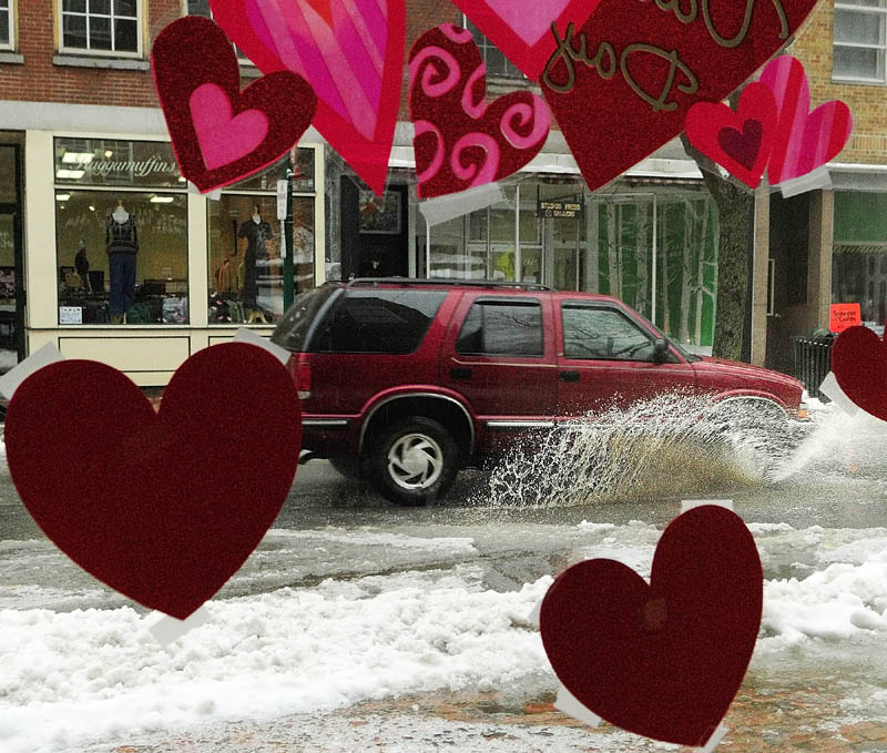 Valentine's Day decorations in the Johnson Hall Performing Arts Center office window frame a vehicle splashing down Water Street in downtown Gardiner on Friday afternoon. The storm had started as snow and switched to sleet and rain as the day went on.