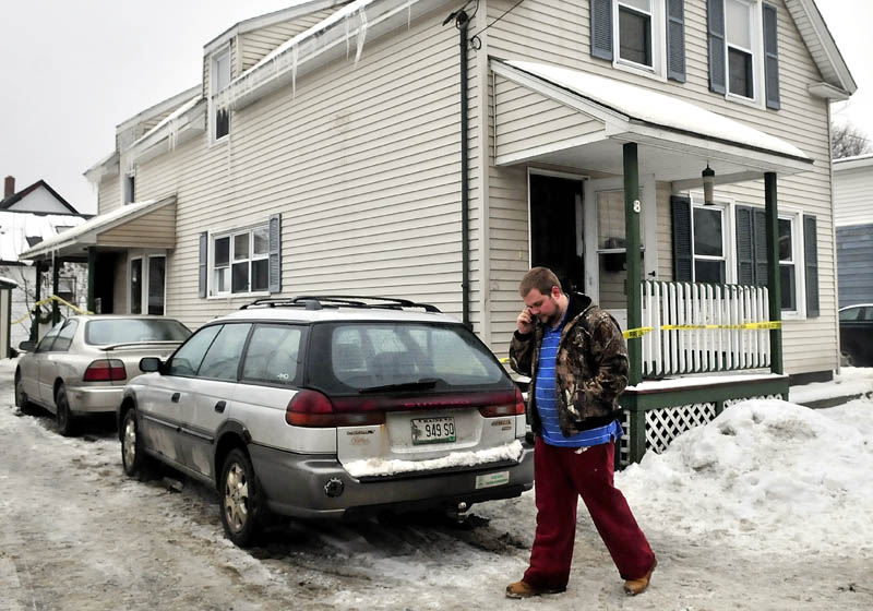 Homeowner Nicholas White speaks on a cellphone outside his home on King Street in Waterville after fire destroyed the interior and belongings shortly after midnight on Monday. White and occupant Jacob Reid said they were in shock later Monday as investigators searched inside for the cause.