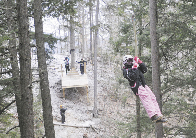 LOOKS LIKE FUN: Hannah Connell, 10, of Orlando, Fla., a moves through the forest on a zip line at Sunday River in Newry last week.