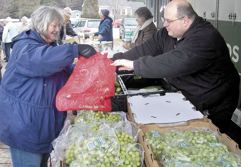 STOCKING UP: Volunteer Ron Meldrum, of New Vineyard, helps June Watson pack grapes at the Good Shepherd Food Bank food giveaway event Thursday morning. Watson, who was collecting food for a social service center in Livermore Falls, was among the 320 people served by the mobile food unit, which handed out 10,000 pounds of food in the parking lot at Fairbanks School Meeting House in Farmington, organizers said.
