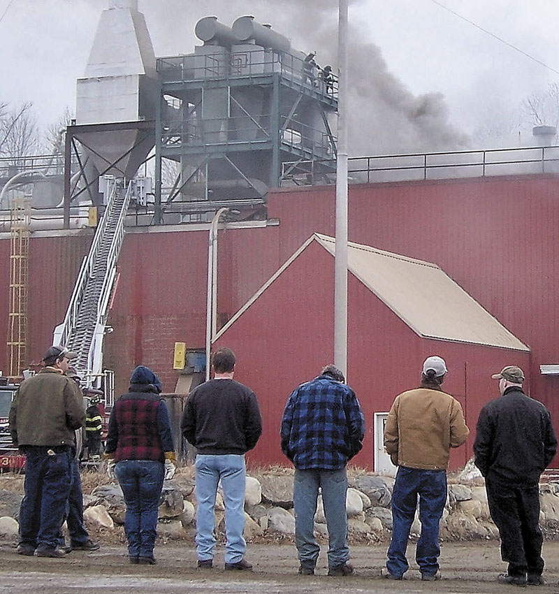 FIRE IN STRONG: Workers watch as smoke billows from the Geneva Wood Fuels plant on Thursday morning. A fire started on the third floor about 8 a.m. and the wood pellet mill, where 21 people work, is expected to reopen in the next few days, company officials said.