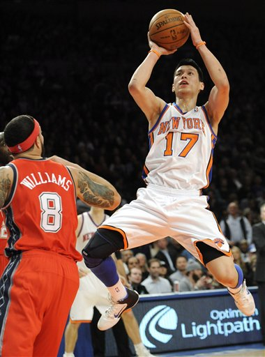 New York Knicks' Jeremy Lin (17) puts up a shot as New Jersey Nets' Deron Williams looks on during the first quarter of an NBA basketball game, Monday, Feb. 20, 2012, at Madison Square Garden in New York. (AP Photo/Bill Kostroun)