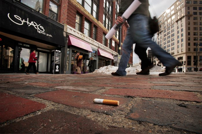 A cigarette butt lies in Monument Square today. Beginning March 7, Portland smokers face a $100 fine for discarding cigarette butts on public property.