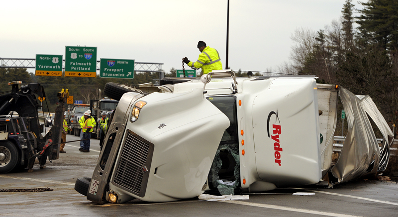 Workers from Stewart's Trucking and Heavy Hauling work on righting a flipped tractor-trailer on the Falmouth spur near the I-295 ramp today. The accident temporarily closed Exit 11 and access to the turnpike.