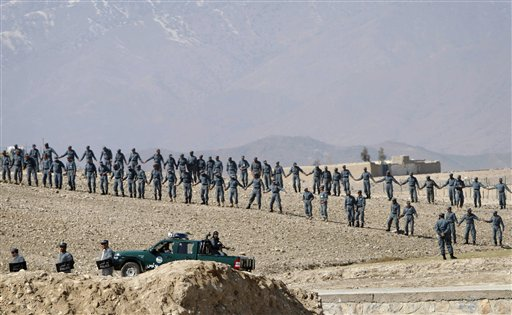 Afghan policemen form a line outside American military base on Thursday during an anti-U.S. demonstration in Mehterlam, Laghman province east of Kabul, Afghanistan. The police fired shots in the air to disperse hundreds of protesters who tried to break into the base to vent their anger over this week's Quran burnings incident.