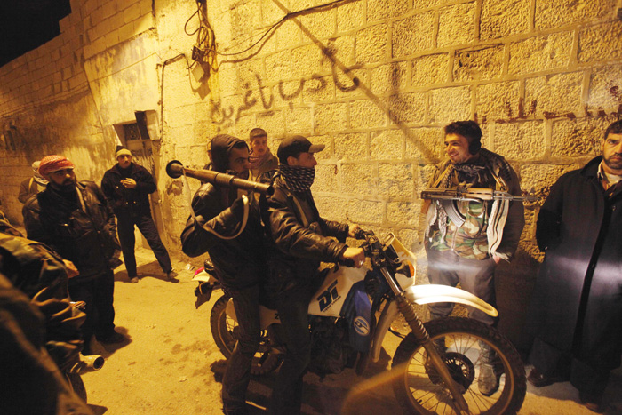 Syrian rebels gather in an alley on Sunday as they secure a demonstration site in Idlib.