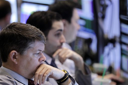 Traders work on the floor at the New York Stock Exchange in New York today as the Dow Jones industrial average crossed the 13,000 mark, and quickly fell back.