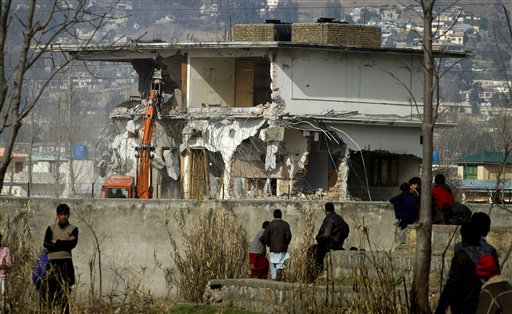 Local residents watch as authorities use heavy machinery to demolish the compound of Osama bin Laden in Abbottabad, Pakistan.
