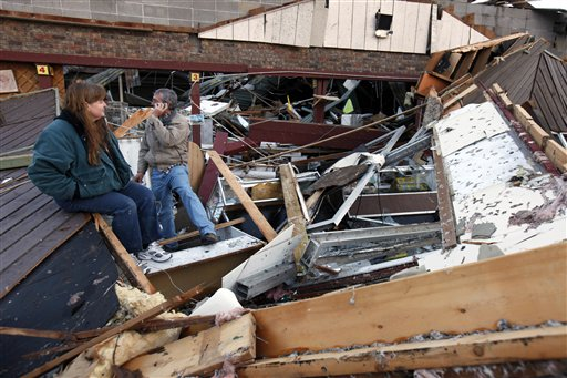 Sherry Cousins and her brother Bruce Wallace sit in the wreckage of their secondhand store in Branson, Mo. today.