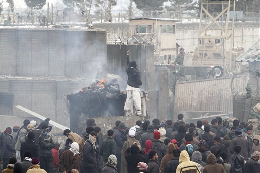 An Afghan protester points toward a U.S. soldier during a demonstration in Bagram, north of Kabul, Afghanistan, today. More than 2,000 angry Afghans, some firing guns in the air, protested against the improper disposal and burning of Qurans and other Islamic religious materials.