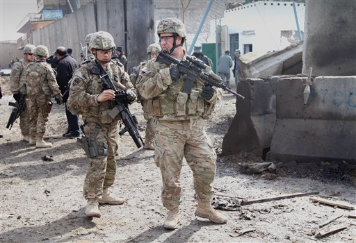 U.S. soldiers who are part of the NATO-led International Security Forces survey the scene of a suicide attack in Kandahar, south of Kabul, Afghanistan today.