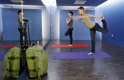 Travelers Maria Poole, right, and Lindsey Shepard, practice yoga at San Francisco International Airport's new Yoga Room recently. The quiet, dimly lit studio officially opened last week in a former storage room. Airport officials believe it is the world's first airport yoga studio.