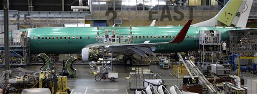 A Boeing employee rides a tricycle past a 737 airplane being assembled at the company's facility in Renton, Wash., in this June 2011 photo.