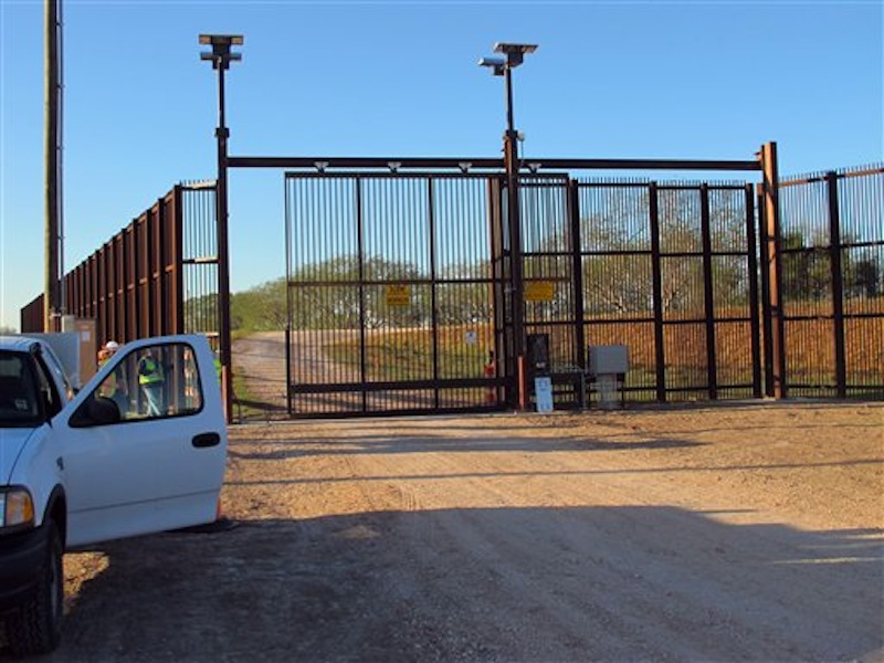 In this Jan. 27 photo, government contractors test a new gate in the border fence in Brownsville, Texas. A year after completion of the border fence the government is installing 44 gates in South Texas. (AP Photo/Chris Sherman)