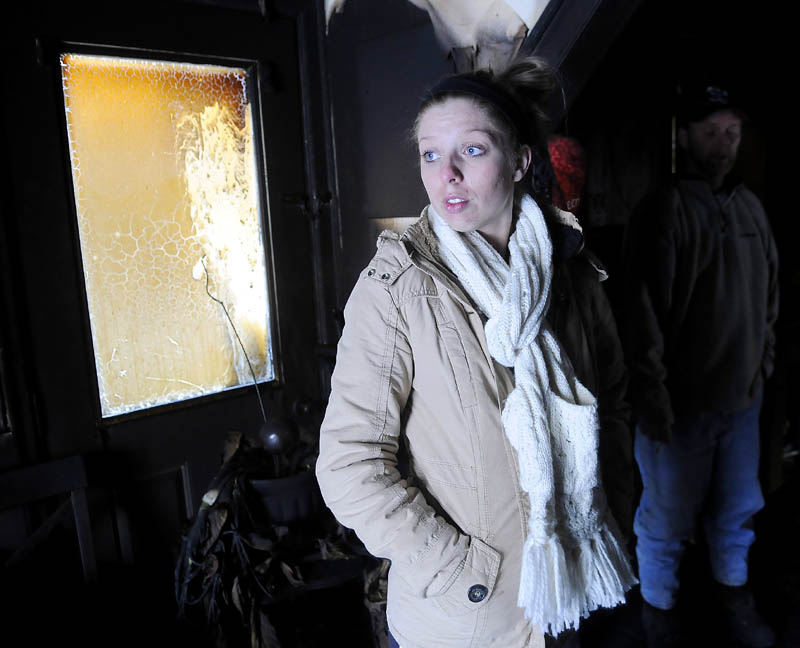 Siera Boucher stands in the burned out kitchen Monday at her Readfield home. Boucher, 21, and her parents Kevin and Noreen Boucher, escaped their burning home Sunday night without injury. The home was gutted by fire.