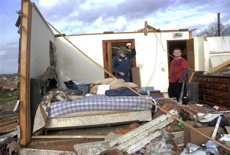 Keith Hucke, left, and Devyn Byrd, 14, survey the damage to Hucke's house after a severe storm hit in the early morning hours on Wednesday, Feb. 29, 2012, in Harrisrbug, Ill. Hucke said he was in his bed when the wall right next to him collapsed during the storm. A severe pre-dawn storm pounded portions of southern Illinois on Wednesday. Nine deaths have been reported in Harrisburg and left the city's medical center scrambling to treat an influx of injured, the hospital's top administrator said. (AP Photo/The Southern Illinoisan)