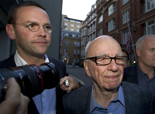 The chairman of News Corp. Rupert Murdoch, right, and his son James in a July 2011 photo. James Murdoch is stepping down as executive chairman of the company's U.K. newspaper arm.