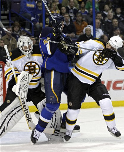 St. Louis Blues' Jason Arnott (44) takes position between Boston Bruins' Joe Corvo (14) and goalie Tim Thomas (30) as they try to avoid a flying puck in the second period of an NHL hockey game, Wednesday, Feb. 22, 2012, in St. Louis. (AP Photo/Tom Gannam)