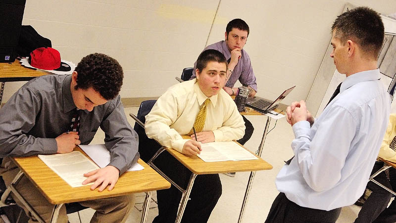 James Thurber, center, asks an intake interview question of business teacher Ryan Wheaton as they practice for a tax preparation clinic. Classmates Micah Adams, left, and Matt Landry look on.
