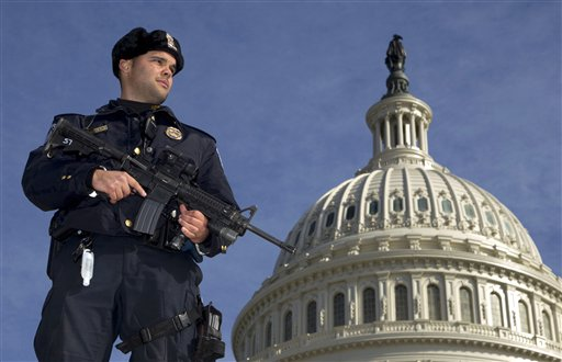 Capitol Police Officer Angel Morales stands guard on the west side of the Capitol in Washington today following the arrest of a 29-year-old terror suspect in an FBI sting operation.