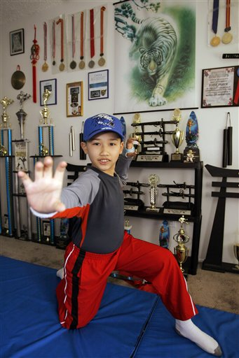 A 2008 photo of Moshe Kai Cavalin, at age 10, striking a martial arts pose at his home studio in Downey, Calif. At age 11, Cavalin became the youngest person ever to earn an Associate in Arts degree from East Los Angeles College and now, at 14, is poised to graduate with honors from UCLA later this year.