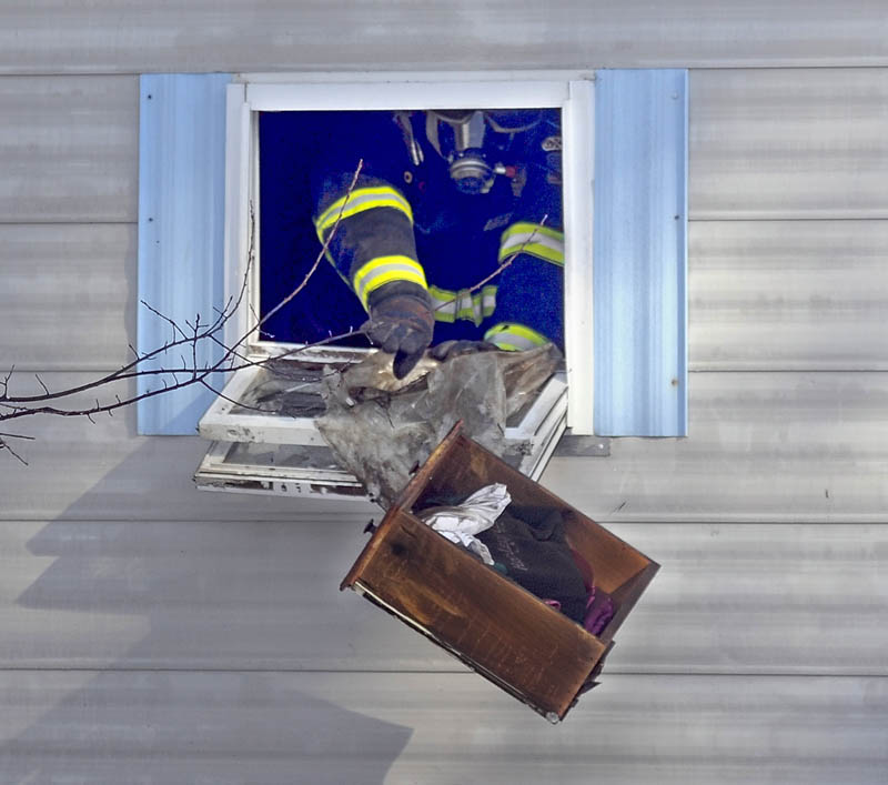 NO INJURIES: A Gardiner firefighter throws out a burned piece of furniture Wednesday from the Sansouci residence in Gardiner. Firefighters saved the home but smoke damaged the interior of the trailer that the family rents.