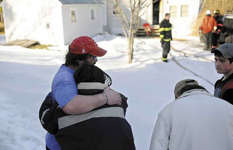 NO INJURIES: Kevin Sansouci comforts his wife, Tracey, after a fire damaged their mobile home Wednesday in Gardiner. Smoke damaged the interior but no injuries were reported. At right are their friend Richard Trask Jr. and his father, Richard Trask Sr.