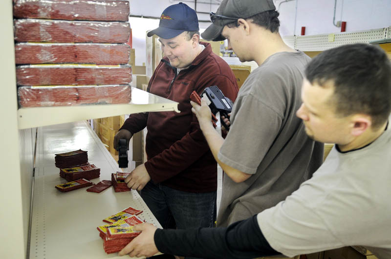 Nick Hamel, right, Selby Landmann, center, and Scott Boucher price firecrackers recently at Pyro City Fireworks on U.S. Route 202 in Manchester. Employees stocked up for the Thursday opening of the first fireworks store in Maine since the ban on fireworks was lifted last year.